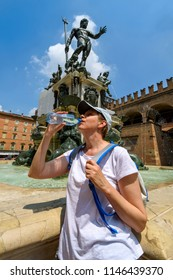 Woman tourist on a hot summer day. He drinks water from a plasti