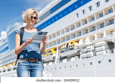Woman tourist on shore looking at map, standing in front of big cruise liner, summer day