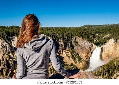 Woman tourist overlooking Lower Falls waterfall in the Grand Canyon of Yellowstone National Park, Wyoming, USA