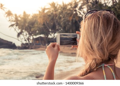 Woman tourist photographing beach sunset on smartphone during beach travel holidays