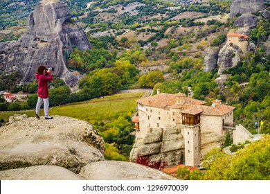 Woman tourist with professional camera taking picture film video from monastery. The Meteora monasteries, Greece Kalambaka.