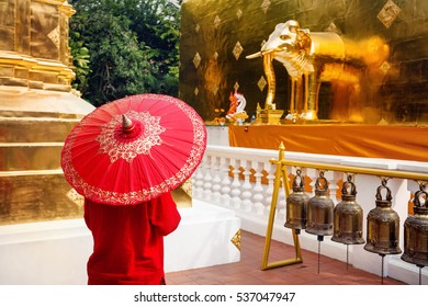 Woman tourist with red traditional Thai umbrella in Golden temple Wat Phra Singh in Chiang Mai, Thailand