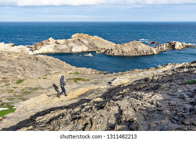 Woman tourist runs down the hill to the sea. Cap de Creus is the easternmost point of Catalonia, mainland Spain and the Iberian Peninsula.