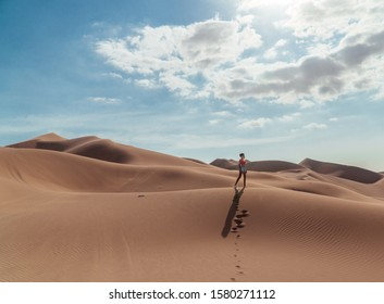Woman tourist in sandy desert. Girl in red in hot sand desert. Fun, Travel, holiday, explore, scenic shot, with sand ripples and footprints. Tourism shot in Huacachina, Peru. Epic, dramatic shot.