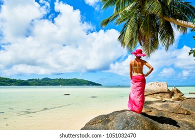 Woman tourist with sarong on tropical beach under palm tree, Anse a La Mouche, Mahe, Seychelles