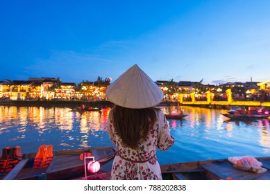 Woman tourist is sightseeing at Thu Bon riverside and wearing Non La (Vietnamese Hat) in Hoi An, Vietnam.