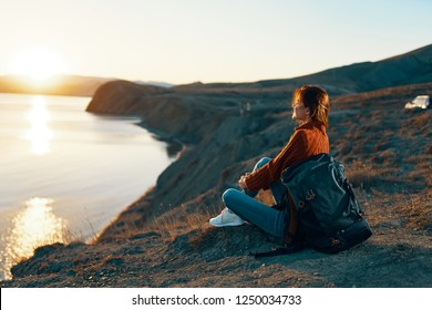 woman tourist sits on the ground admiring the sunset                        - Shutterstock ID 1250034733
