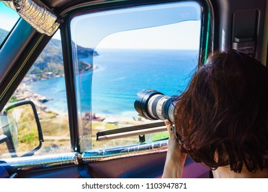 Woman tourist sitting in camper car taking photo with camera on seacoast. Greece Peloponnese.