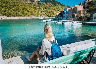 Woman tourist sitting on the bank in front of beautiful sea bay on summer morning. Lovely vacation in Assos village with beautiful traditional houses and pine groove. Kefalonia, Greece