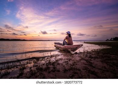 Woman tourist sitting on boat at the Sirindhorn Dam at Pattaya Noi (Little Pattaya) beach in Ubon Ratchathani.