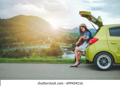 Woman tourist sitting on hatchback car and playing guitar  background is mountain.Asia traveler young girl enjoying on holiday.