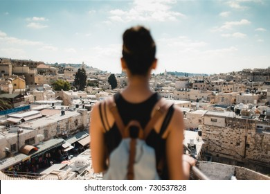 Woman tourist standing with backpack overlooking Jerusalem city