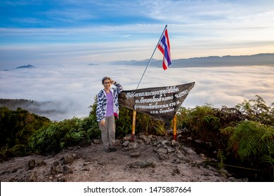 Woman tourist standing at viewpoint of Gunung Silipat. Thai language is name of viewpoint and show metres above sea level MSL. Relaxation and travel concept.