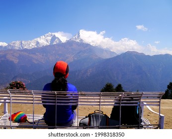 the woman tourist take a seat on poonhill, looking at the himalayan mountains view.