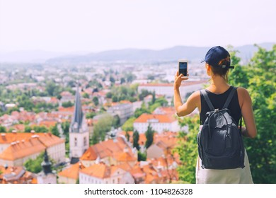 Woman tourist takes a picture panoramic view with red roofs of Ljubljana from Castle on smart phone. Girl traveler with backpack discovers Slovenia. Springtime or Summer in Europe. Travel and Vacation