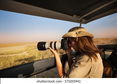 Woman tourist taking photo of African savannah