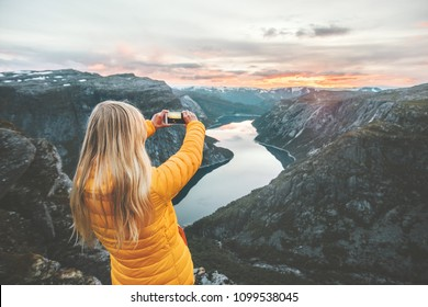 Woman tourist taking photo by smartphone on mountain top traveling in Norway adventure lifestyle active vacations modern technology connection concept