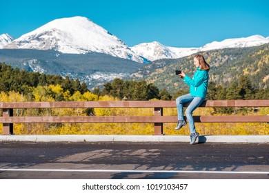 Woman tourist taking photo. Season changing from autumn to winter. Rocky Mountains, Colorado, USA.