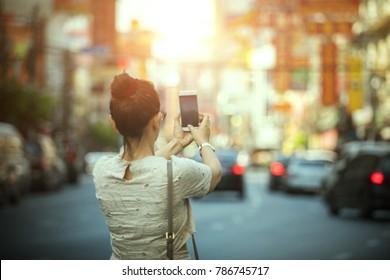 woman tourist taking a photograph with smart phone in yaowarat china town bangkok thailand