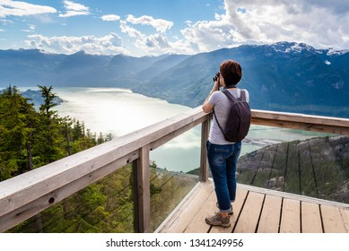 Woman Tourist Taking Photos from a Viewing Platform on the Top of a Mountain. Impressive Mountain ana Sea Scenery. Squamish, BC, Canada.