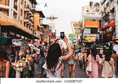 Woman tourist taking pictures with her cell phone on street in blurred background