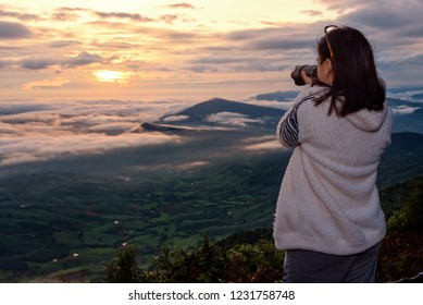 Woman tourist are using a DSLR camera photographing nature landscape the sun fog mountain in the winter during sunrise on high viewpoint at Phu Ruea National Park, Loei province, Thailand