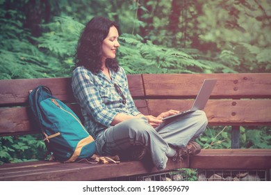 Woman tourist using a laptop in the park