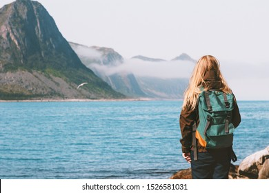 Woman tourist walking alone enjoying sea view outdoor travel vacations lifestyle girl with backpack in Norway