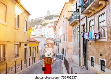 Woman tourist walking back on the narrow street in Alfama region during the morning light in Lisbon, Portugal