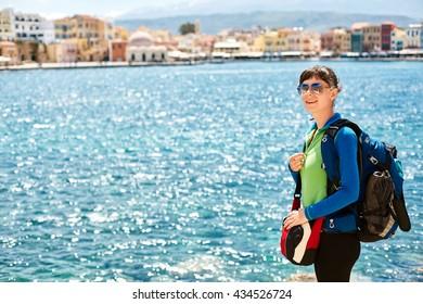 woman tourist walking on the waterfront of Chania bay backround, Crete, Greece