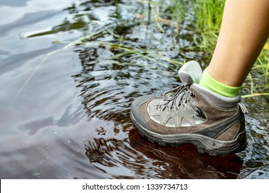 Woman in tourist waterproof hiking boots walks through the water in puddles. Close-up.