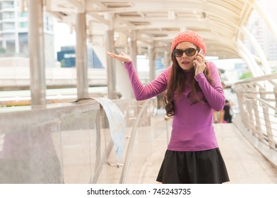 Woman tourist wear wool hat sun glasses in purple sweater and black short skirt use smart phone calling someone to ask the direction when she get lose the way in city.