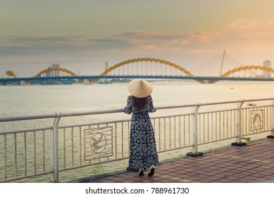Woman tourist is wearing Non La (Vietnamese hat) and looking at the river view with Dragon bridge in Danang, Vietnam.