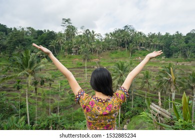 A woman tourist who clothed in vintage style dress is standing at rice terrace, one of famous landmark in Bali - Ubud. Concept of freedom travel and relaxation feeling.