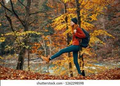 Woman tourists walks through the autumn forest