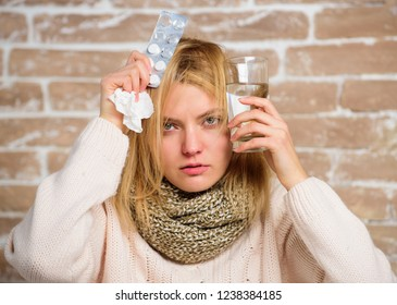 Woman tousled hair scarf hold glass water and tablets blister. Girl suffer fever and take medicine. Headache and fever remedies. Take medications to reduce fever. What to know about breaking fever.