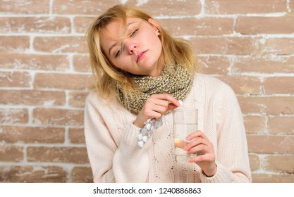 Woman tousled hair scarf hold glass water and tablets blister. Girl feels ill suffer fever and take medicine. Headache and fever remedies. Pills for breaking fever. Take medications to reduce fever.