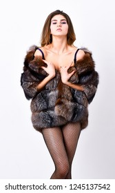 Woman tousled hairstyle posing lingerie and fur jacket. Fashion boutique concept. Fashion for female. Elite clothes for sensual girl. Fashion luxury design. Girl temptress wear stockings and fur coat.