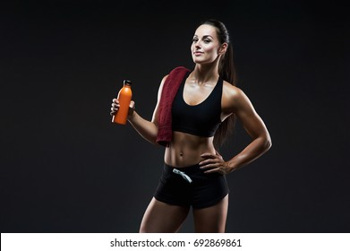 Woman with towel drinking water from aluminum bottle in gym fitness. Sport, drink and lifestyle concept