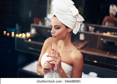 Woman with towel holding glass of champagne in bathroom