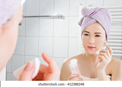 Woman with towel on head applying toner on her face at the bathroom