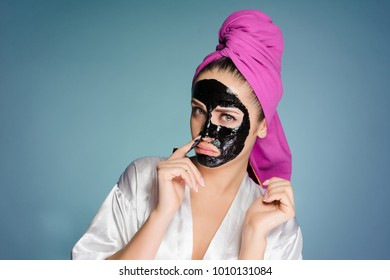 woman with a towel on her head applied a mask to the skin of her face