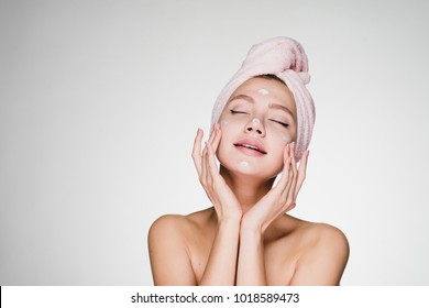 woman with a towel on her head puts cream on her face