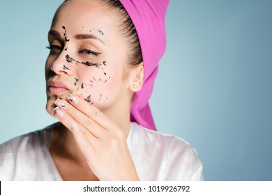 a woman with a towel on her head removes the cleansing mask from her face
