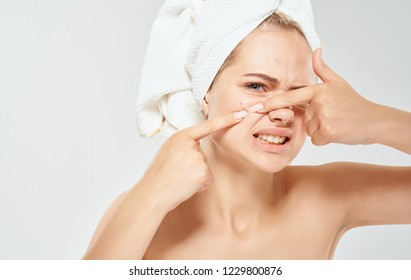 woman with a towel on her head squeezes acne on her face