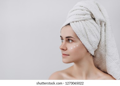 Woman with a towel on her head  looking above with face  moisturizer near eyes. Causing moisturizer cream onto her face. Intimate girl with perfect and healthy skin  on white background.