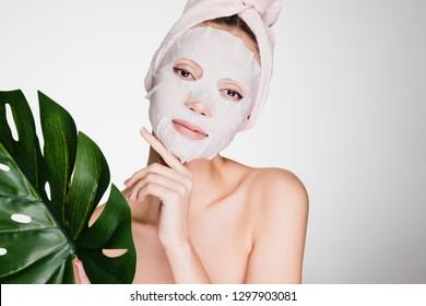 woman with a towel on her head applied a cleansing mask on her face on a gray background