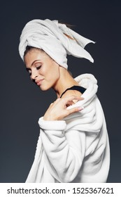 Woman with a towel on her head a white bathrobe and a dark background