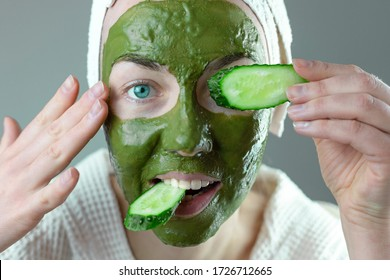 woman with a towel on her head makes a cosmetic face mask of green clay with cucumbers. funny home spa concept.