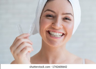 A woman with a towel on her head holds a whitening mouth guard for teeth. The girl aligns her teeth with the help of transparent night removable retainers. Orthodontic device for a perfect smile.